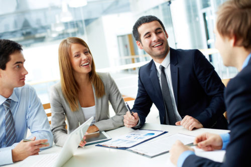 Image of business partners laughing during interaction at meeting